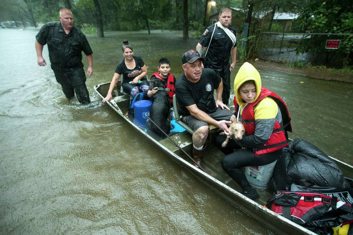 Splendora Police officers Lt. Troy Teller, left, and Cpl. Jacob Rutherford guide a boat carrying Maria, Ramiro, Jr., Ramiro and and Veronica Lopez from their flooded neighborhood inundated by rains from Tropical Depression Imelda inundates the area on Thursday in Spendora, Texas.