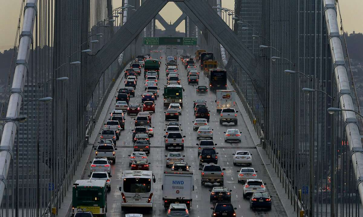 FILE - In this Dec. 10, 2015, file photo, vehicles make their way westbound on Interstate 80 across the San Francisco-Oakland Bay Bridge as seen from Treasure Island in San Francisco. California Gov. Gavin Newsom, Attorney General Xavier Becerra and others plan to announce legal action Wednesday, Sept. 18, 2019, to fight the Trump administration's move to revoke the state's authority to set auto mileage standards. (AP Photo/Ben Margot, File)