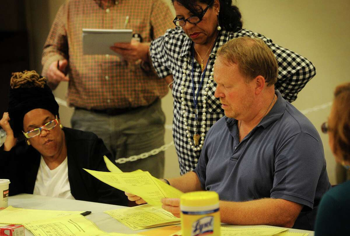 Absentee ballot head moderator Tom Errichetti, right, and deputy moderator Rosalina Roman-Christy, center, look over absentee ballots during a recount of results from last week's primary at the Margaret Morton Government Center in Bridgeport, Conn. on Wednesday, September 23, 2015.