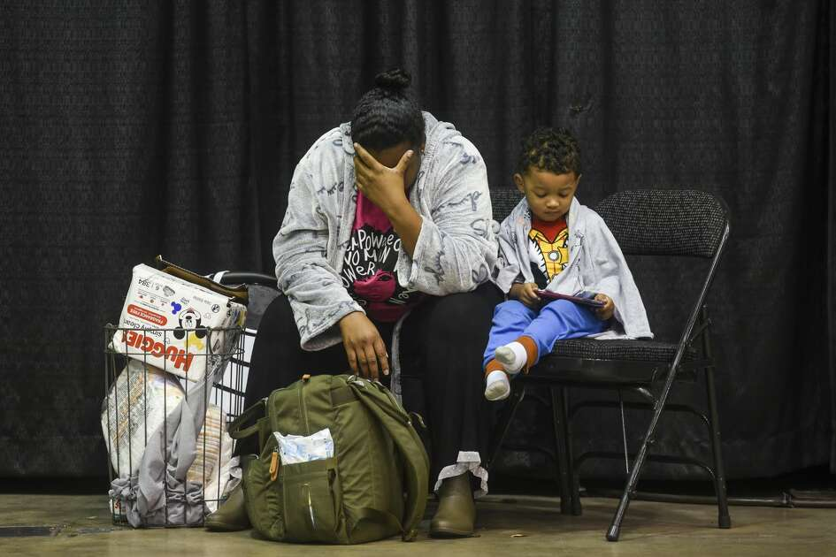 Alexis rests her head as her son, two-year-old Chase, plays on a cellphone in the Beaumont Civic Center in Beaumont, Texas Thursday morning. Alexis says she woke up at 3 a.m. to water near their front door of their apartment and by 6 a.m. were leaving with all they could carry to the emergency shelter. Photo taken on Thursday, 09/19/19. Ryan Welch/The Enterprise