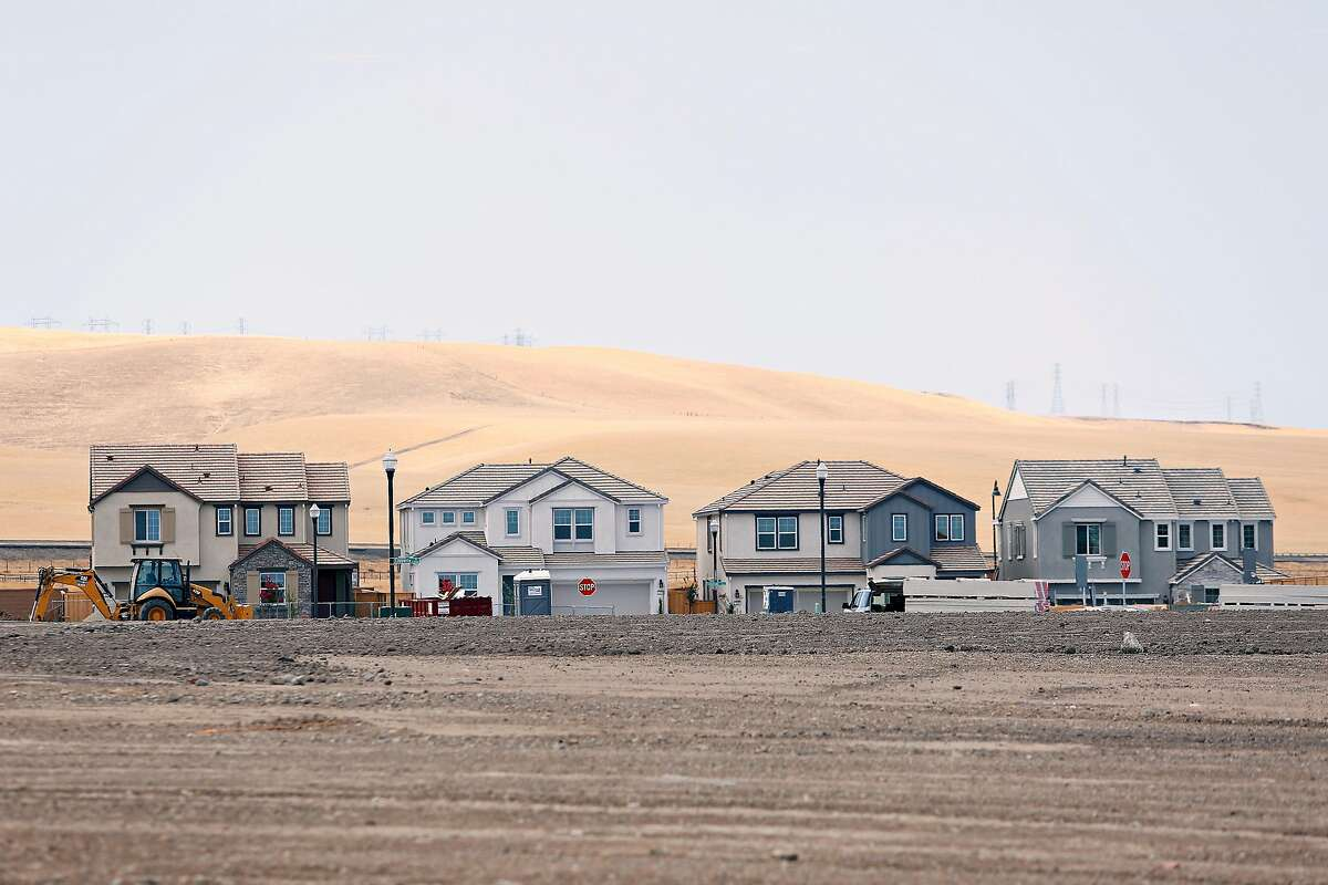 New homes being built are seen between hills in Tracy (background) and land to be developed (foreground) at Tracy Hills on Thursday, September 5, 2019 in Tracy, CA.