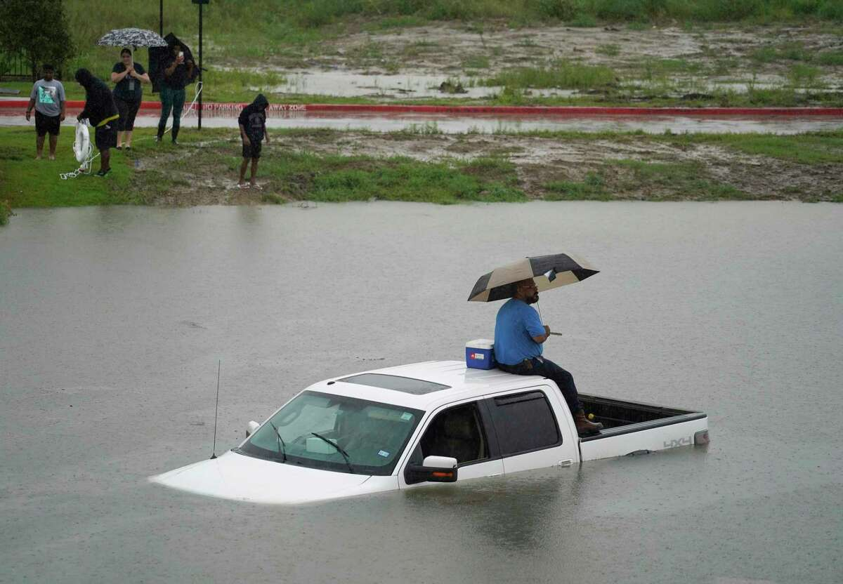 A man sits on top of a truck on the flooded feeder road along Sam Houston Tollway West between Wilson and Ralston Rd. near Garners Bayou while people try to toss him a life preserver ring Thursday, Sept. 19, 2019, in Houston. Members of the Houston Fire Dept. brought him a life jacket and walked him to dry land.