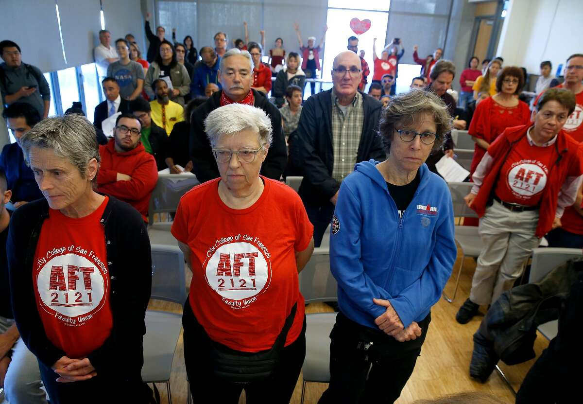 Faculty and students stand to show disapproval of a proposed pay raise for college executives at a meeting of the CCSF Board of Trustees Budget and Audit Committee at the Chinatown campus in San Francisco, Calif. on Thursday, Sept. 19, 2019.