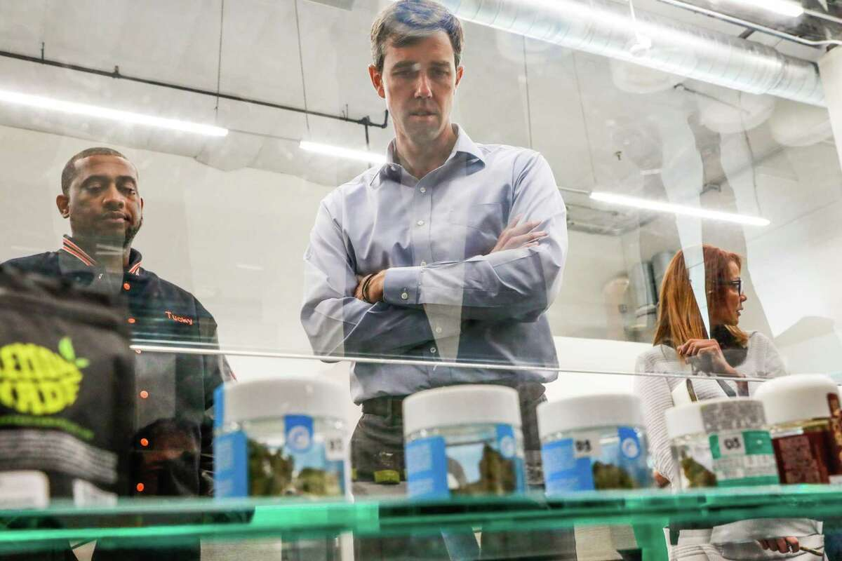 Presidential candidate Beto O'Rourke (center) looks down at cannabis for sale while taking a tour of Blunts and Moore in Oakland, California, on Thursday, Sept. 19, 2019.