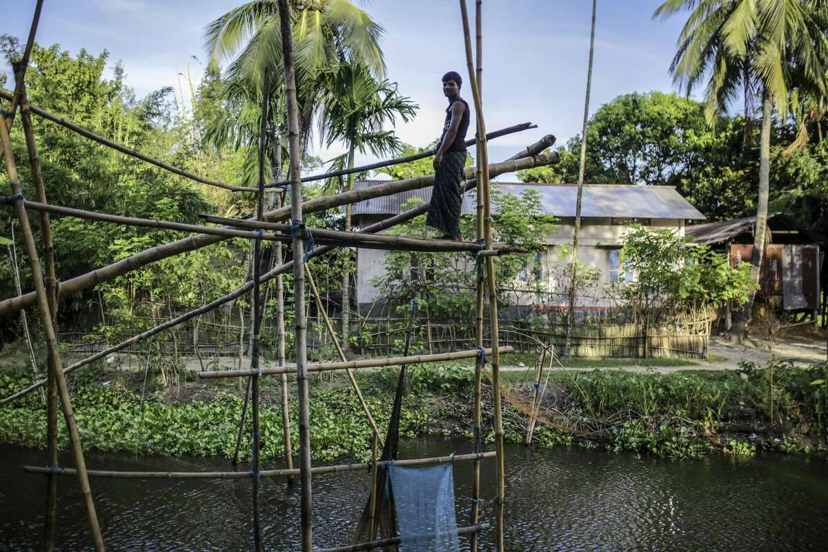 A man stands on bamboo fishing structure in a village of Nalbari district, Assam, India, on Sunday, Sep. 1, 2019. A sense of betrayal and anger is growing in Muslim communities, which are most affected by the National Register of Citizens that aims to separate genuine citizens from illegal migrants. Instead, the country's biggest and most complex registry is dividing families and causing ripples across the political spectrum, fueled by concerns Prime Minister Narendra Modi's party is using the measure to advance a hardline Hindu agenda.