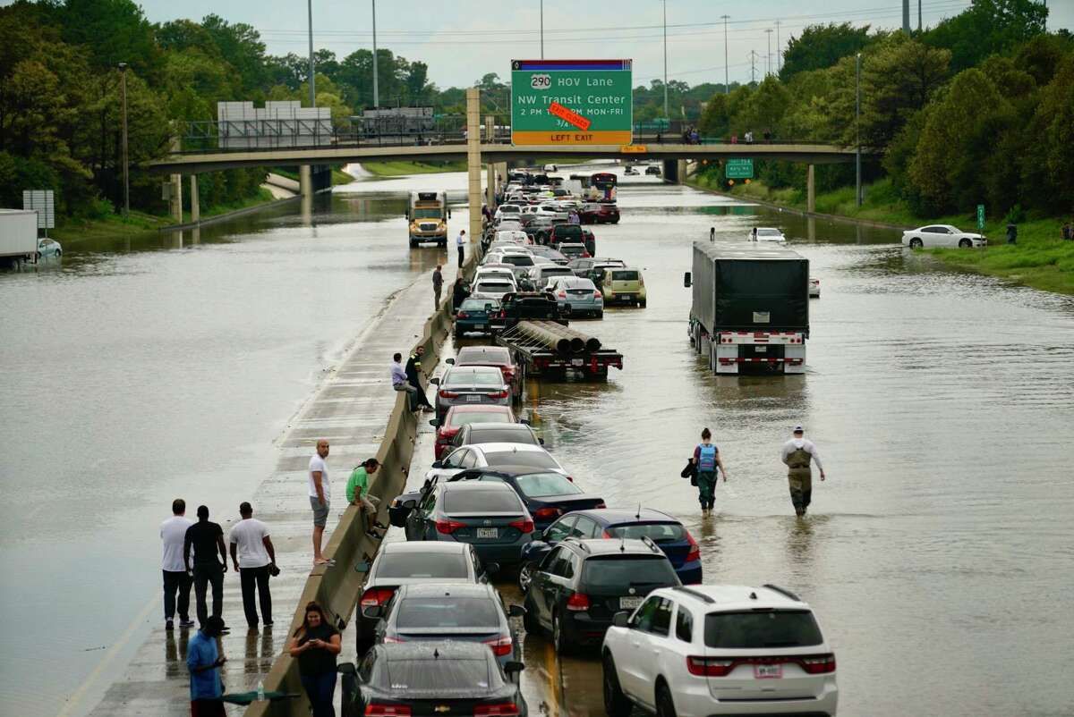 People wait outside of their stranded vehicles along Interstate 10 westbound at T.C Jester, Sept. 19, 2019. The freeway is closed because of high water east bound on the freeway.