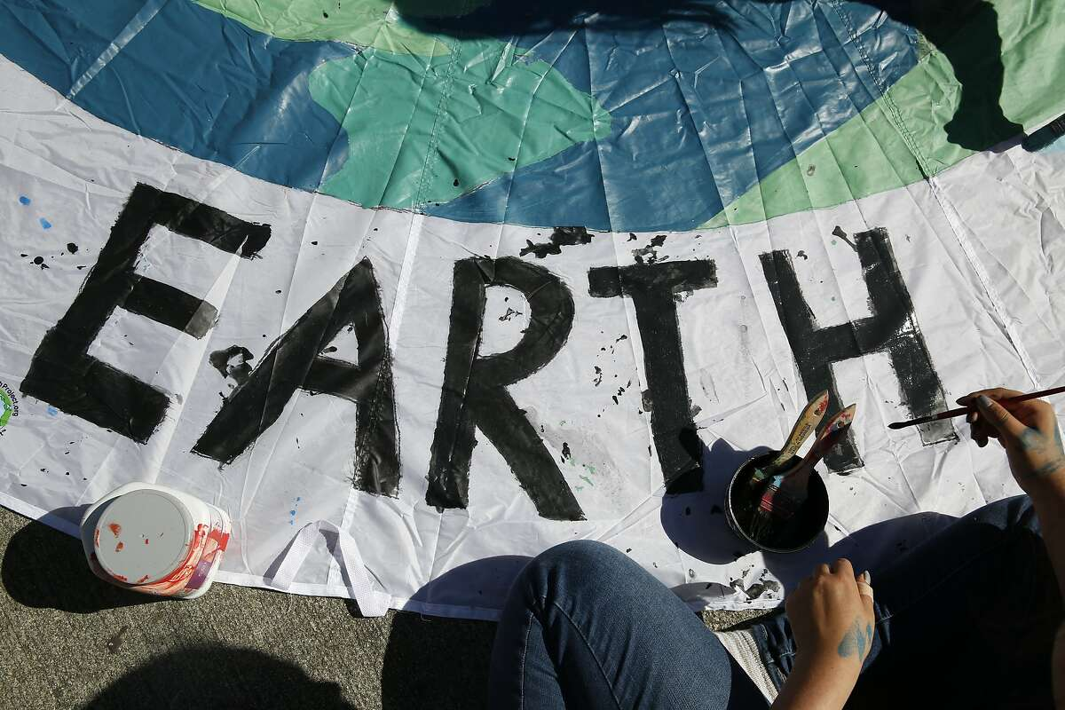 Sakura Martin of Ruth Asawa School of the Arts in San Francisco puts the finishing touches on his sign for the Global Climate Strike march.