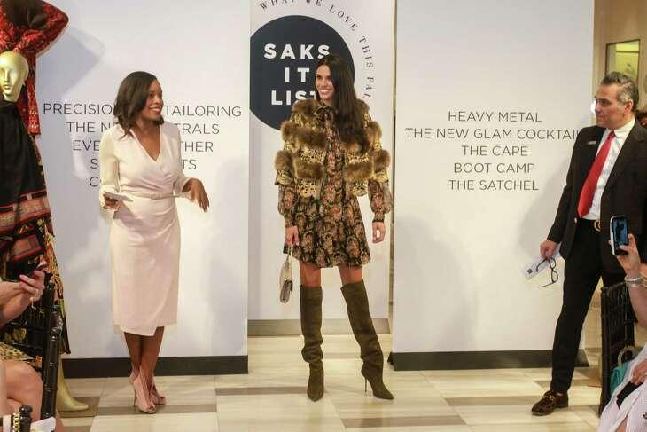 "Saks Fifth Avenue's Fall Trends ""It List"" Luncheon hosts Amber Elliott, left, and Albert Rubio flank a model wearing an Oscar de la Renta printed dress, Rindi fur cape, Giueseppe Zanotti boots and a Nancy Gonzalez bag."