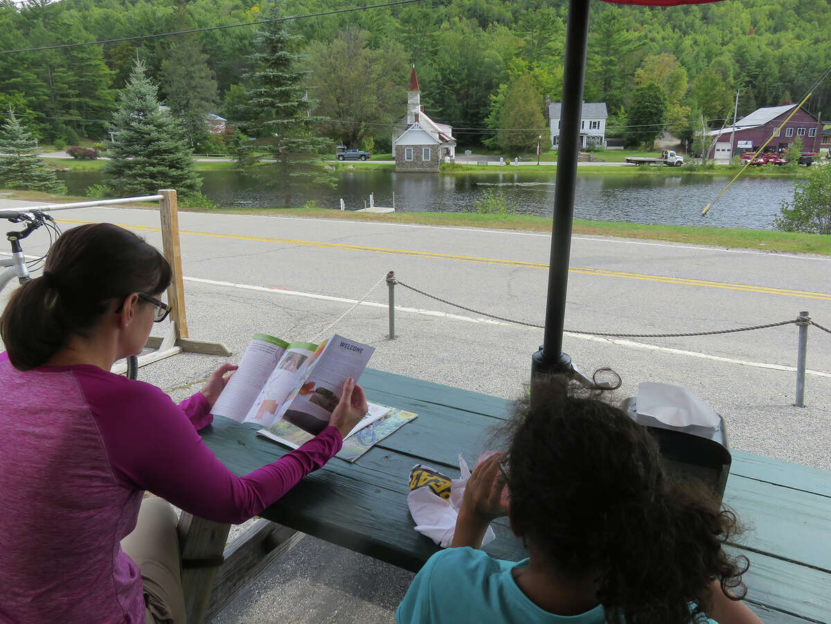 The outdoor tables at the Hub are a place to watch bikes going by. Gillian Scott and her daughter take in the view while waiting for lunch. (Herb Terns / Times Union)