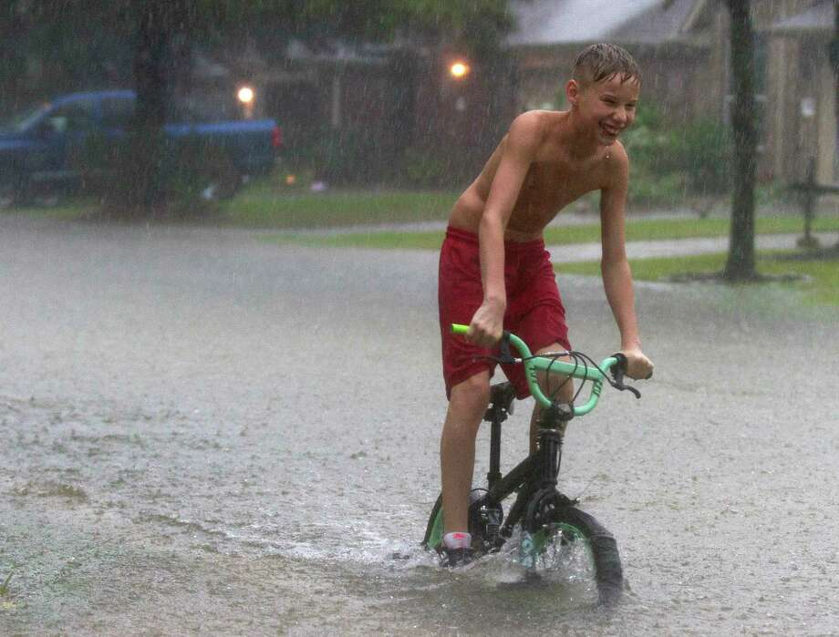 A kid rides his bike near Kings Manor Drive as rain from Tropical Depression Imelda inundate the area, Thursday, Sept. 19, 2019, in Kingwood. Photo: Jason Fochtman, Houston Chronicle / Staff Photographer / Houston Chronicle