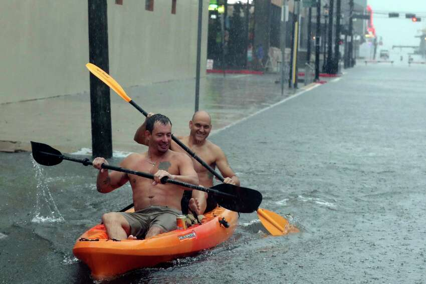 Daniel Collins, front, and Andrew Dominguez paddle their kayak down a flooded 23rd Street near The Strand in Galveston, Texas, Thursday, Sept. 19, 2019, as rains from Tropical Depression Imelda inundated the island. (Kelsey Walling/The Galveston County Daily News via AP)