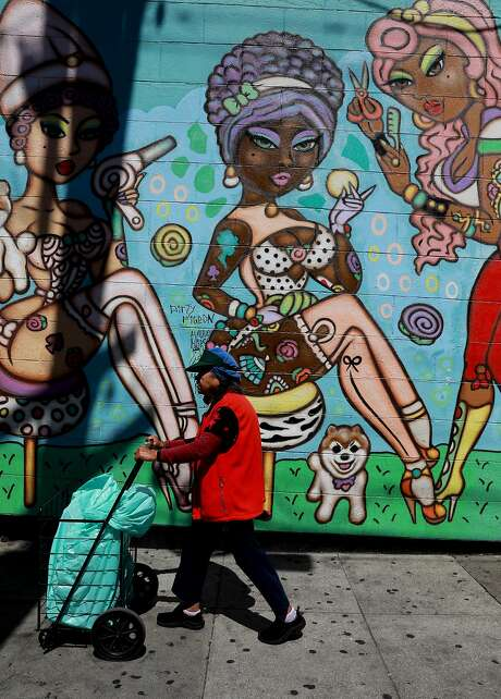 A woman passes a mural on Beauty Bar, at 19th and Mission streets, in S.F. The mural, painted in 2015 by Deb Fineberg, has many of her signature visuals: bright colors and a hyper-feminine vibe. Photo: Yalonda M. James / The Chronicle