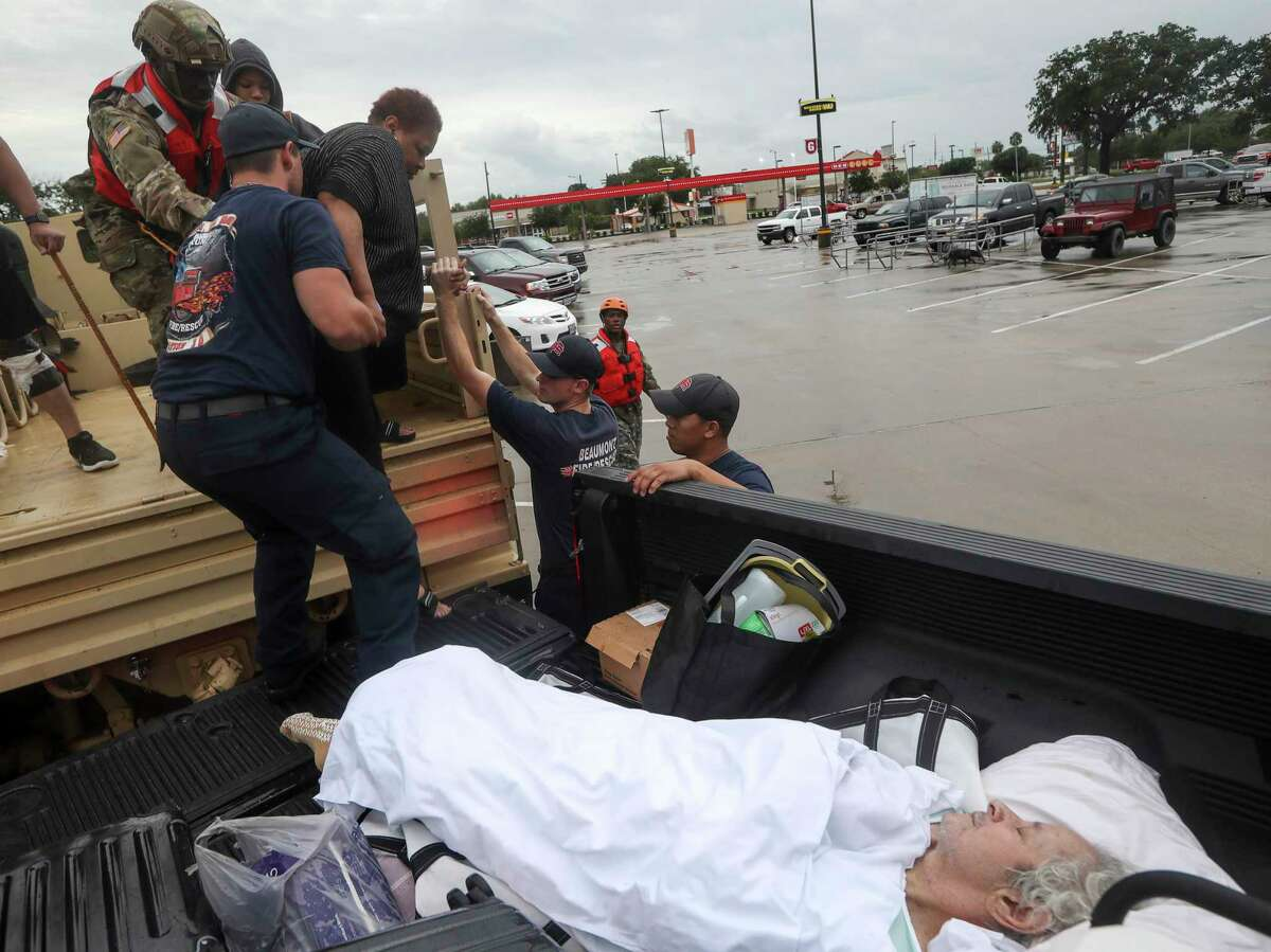 Dwain Kaufman, right, waits for his wife as she is helped into the back of a family member's truck by Beaumont firefighters and members of the Texas National Guard on Thursday, Sept. 19, 2019, in Beaumont.