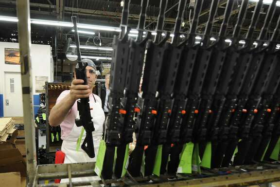 Sergio Pereira adds a completed Colt rifle to a rack of newly assembled guns at the company headquarters in West Hartford in this 2013 file photo. The company said Thursday it was suspending production of AR-15 rifles for the civilian market. (Michael McAndrews/Hartford Courant/TNS)