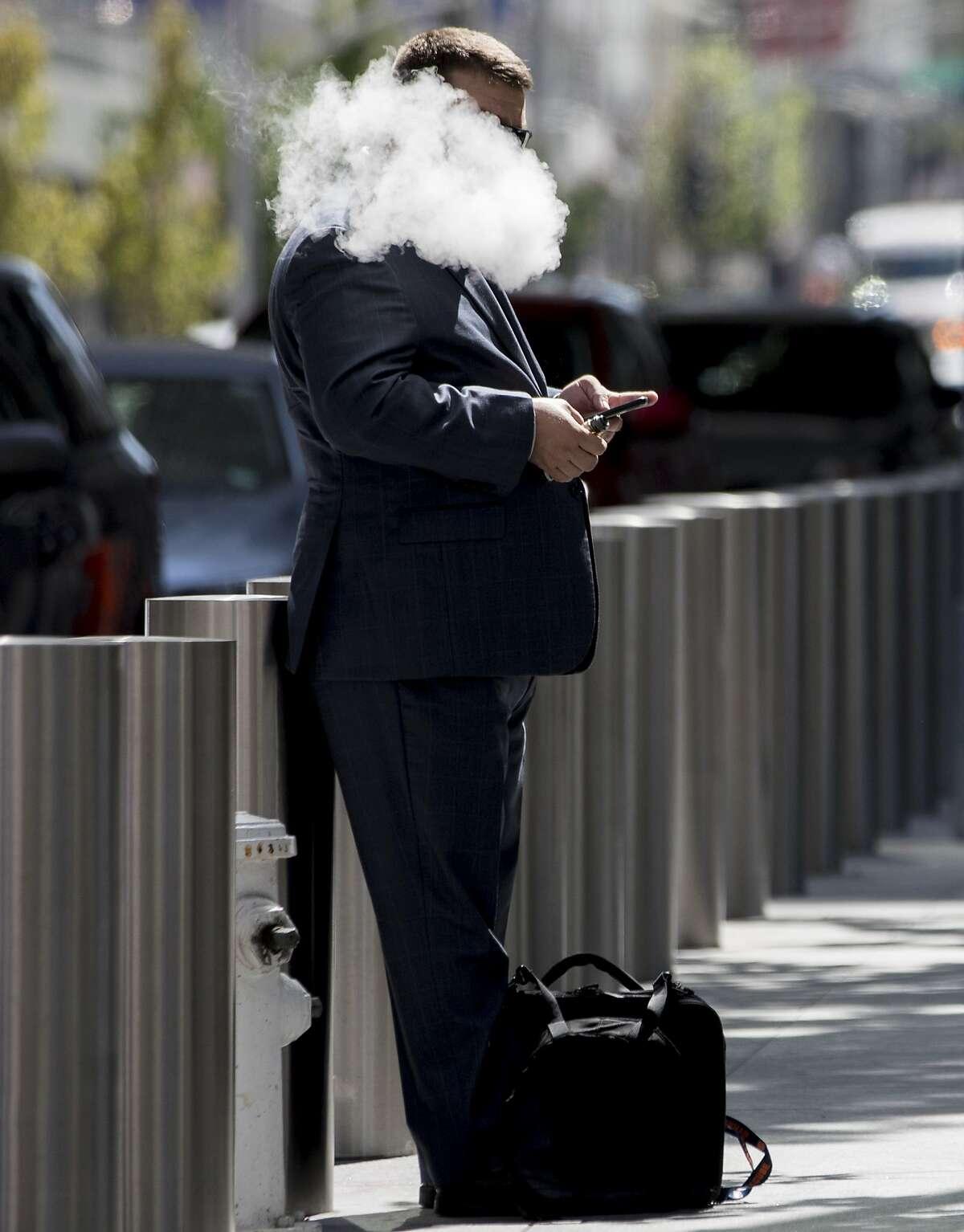 A man smokes an e-cigarette outside of the Transbay Transit Center in San Francisco, Calif. Thursday, September 19, 2019.