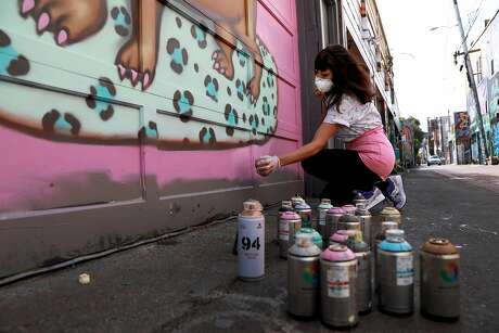 Deb Fineberg uses cans of spray paint as she works on a mural in Lilac Alley near 24th and Mission streets in S.F. Photo: Yalonda M. James / The Chronicle