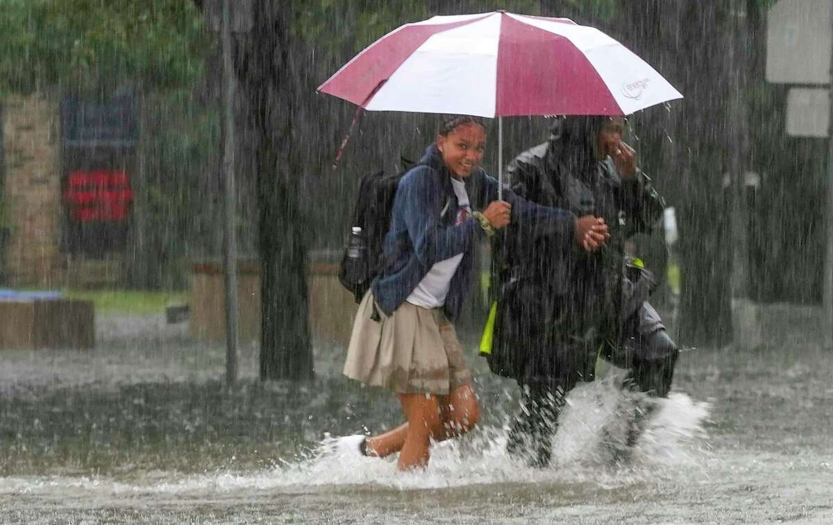 A student leaves Hamilton Middle School as Imelda works its way through the Heights area of Houston, flooding streets on Thursday, Sept. 19, 2019.