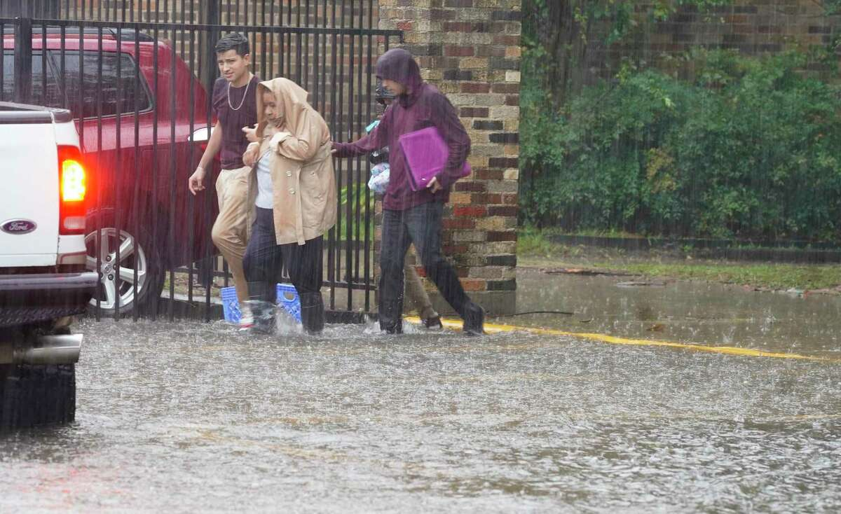 A woman is walked out of Hamilton Middle School as Imelda works its way through the Heights area of Houston, flooding streets on Thursday, Sept. 19, 2019.