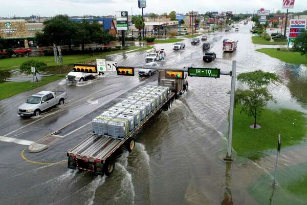 Traffic moves slowly along a flooded College Street Thursday after Tropical Storm Imelda hit Southeast Texas. Photo taken Thursday, 9/19/19