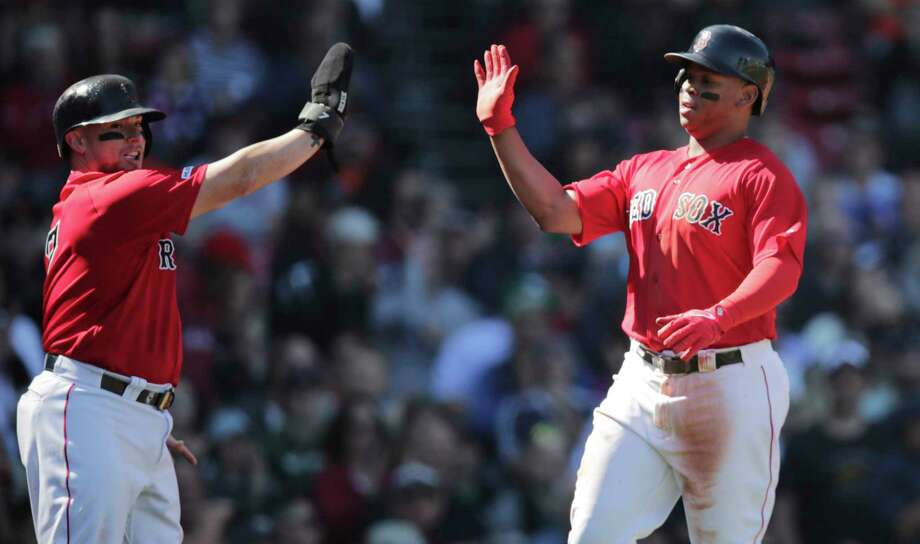 Boston Red Sox's Christian Vazquez, left, and Rafael Devers high-five after scoring on an Xander Bogaerts two RBI single during the second inning of a baseball game against the San Francisco Giants at Fenway Park in Boston, Thursday, Sept. 19, 2019. (AP Photo/Charles Krupa) Photo: Charles Krupa / Copyright 2019 The Associated Press. All rights reserved.