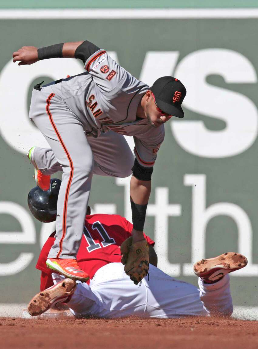 San Francisco Giants second baseman Cristhian Adames, top, steps on the foot of Boston Red Sox's Rafael Devers, while trying unsuccessfully to make the tag during the second inning of a baseball game at Fenway Park in Boston, Thursday, Sept. 19, 2019. (AP Photo/Charles Krupa)