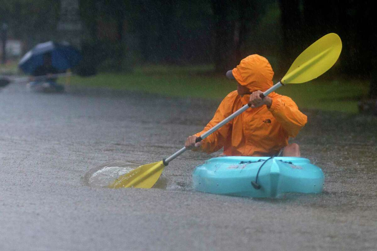 A man uses a kayak to navigate Kings Manor Drive as rain from Tropical Depression Imelda inundate the area, Thursday, Sept. 19, 2019, in Kingwood.