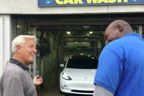 Mark Curtis, founder and CEO of Splash Car Wash, at left, is shown at the Greenwich company's Darien location, joking with Omar Locke, a manager.