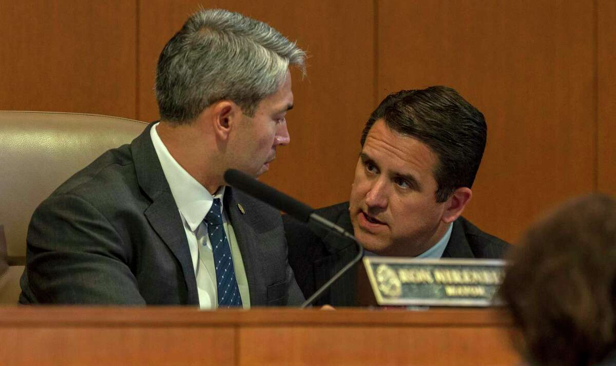San Antonio mayor Ron Nirenberg and City Manager Erik Walsh, left, confer Thursday, Sept. 19, 2019 at city council chambers during a review of proposed changes to the city's paid sick leave ordinance. Walsh announced Thursday he is reorganizing the city's Transportation and Capital Improvements department into two new agencies.