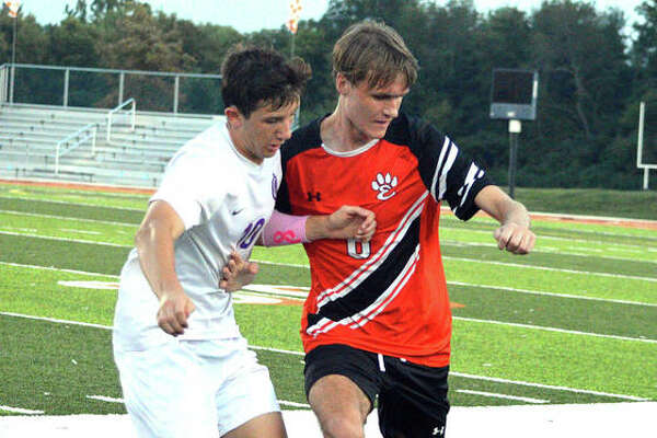 Edwardsville's Alan Ebert, right, battles for the ball with a Collinsville player during the first half of Thursday's game at the District 7 Sports Complex.