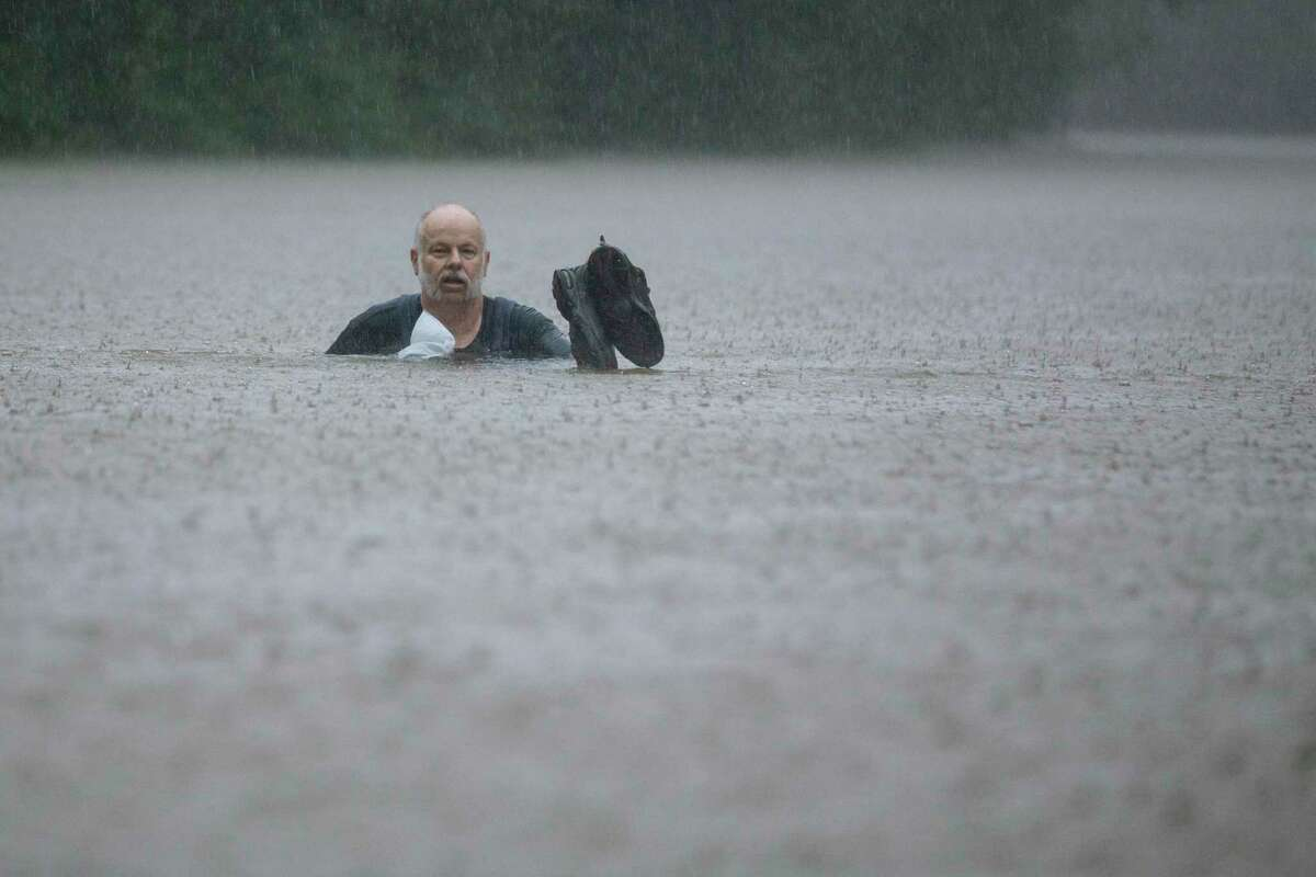 A man wades out through floodwaters caused by heavy rain spawned by Tropical Depression Imelda inundates the area on Thursday, Sept. 19, 2019, in Patton Village.
