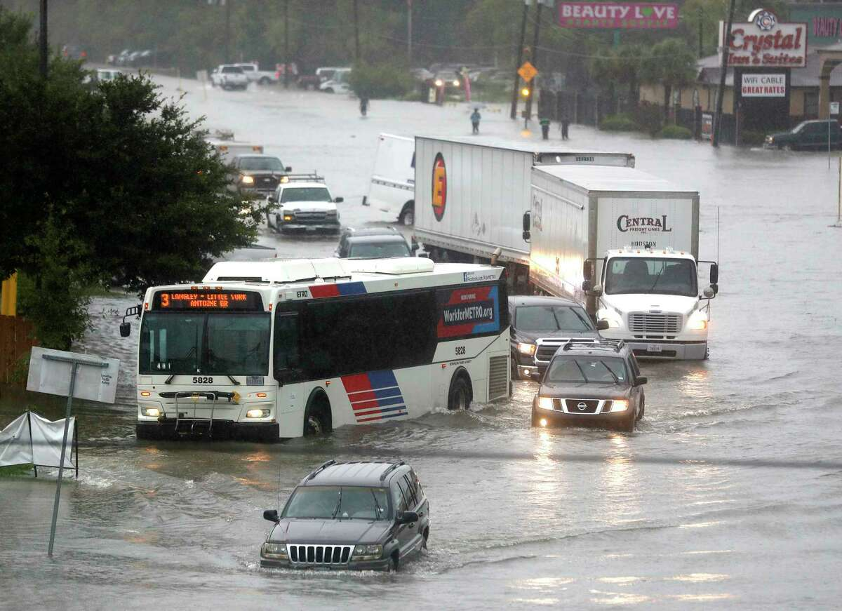 Cars and trucks try to navigate the floodwaters at the intersection of I-59 North and Little York Road as rain poured from the remnants of Imelda, Thursday, Sept. 19, 2019, in Houston.