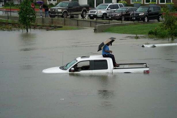 Un hombre se sienta en la parte superior de su camioneta en un camino inundado de Houston, el jueves 19 de septiembre de 2019.