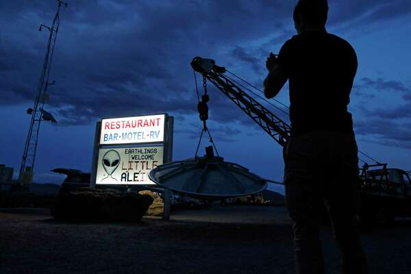 """A man takes a picture of a sign at the Little A'Le'Inn during an event inspired by the """"Storm Area 51"""" internet hoax, Thursday, Sept. 19, 2019, in Rachel, Nev. Hundreds have arrived in the desert after a Facebook post inviting people to """"see them aliens"""" got widespread attention and gave rise to festivals this week."""