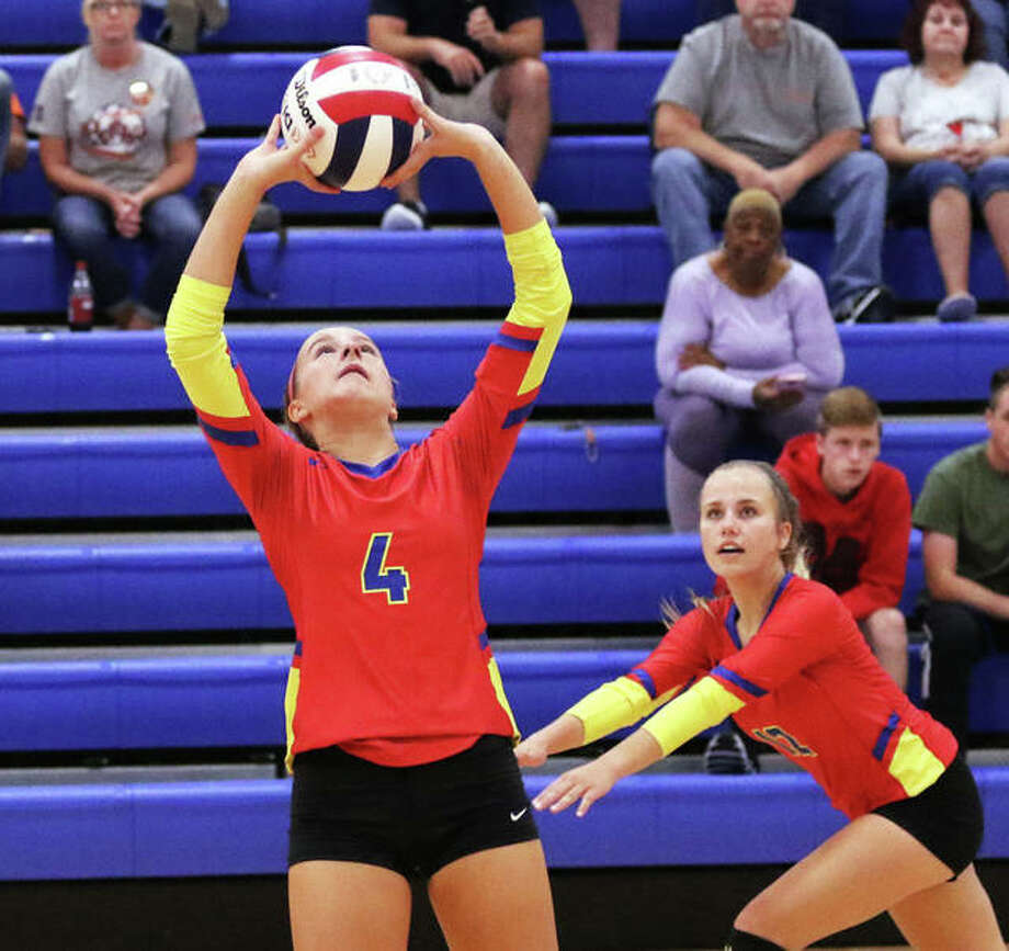 Roxana's Macie Lucas (4) sets while teammate Olivia Mouser heads to the net during the second set against Pana on Thursday night at Roxana Junior High. Photo: Greg Shashack / The Telegraph