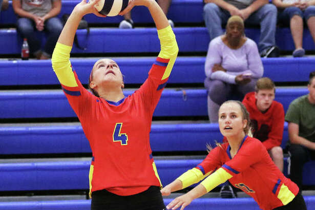 Roxana's Macie Lucas (4) sets while teammate Olivia Mouser heads to the net during the second set against Pana on Thursday night at Roxana Junior High.