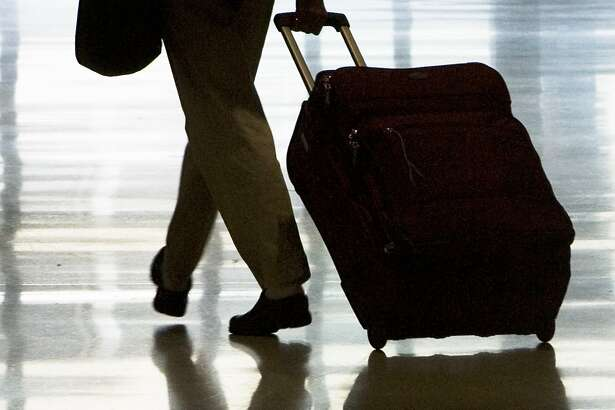 FILE - In this May 21, 2008 file photo, a person is seen rolling luggage at Philadelphia International Airport, Philadelphia. Spirit Airlines said Tuesday April 6, 2010, it will charge as much as $45 each way for a carry-on bag, adding a fee that bigger airlines have yet to try. (AP Photo/Matt Rourke, file)