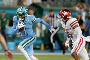 Tulane wide receiver Jalen McCleskey runs with reception in front of Houston cornerback Damarion Williams (6) on the way to the go-ahead touchdown during the final minute of an NCAA college football game in New Orleans, Thursday, Sept. 19, 2019. Tulane won 38-31. (AP Photo/Gerald Herbert)
