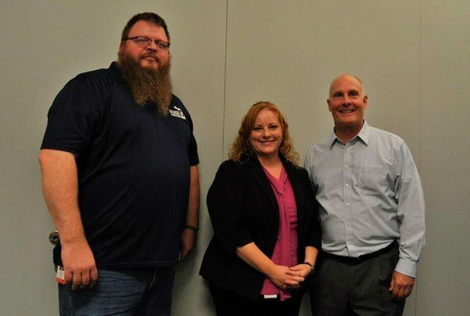 Board Member Brad Blanchard, Executive Director Sarah Kile and Congressman John Moolenaar pose for a photo at 211 Northeast Michigan's office in Midland. (Ashley Schafer/Ashley.Schafer@hearstnp.com)