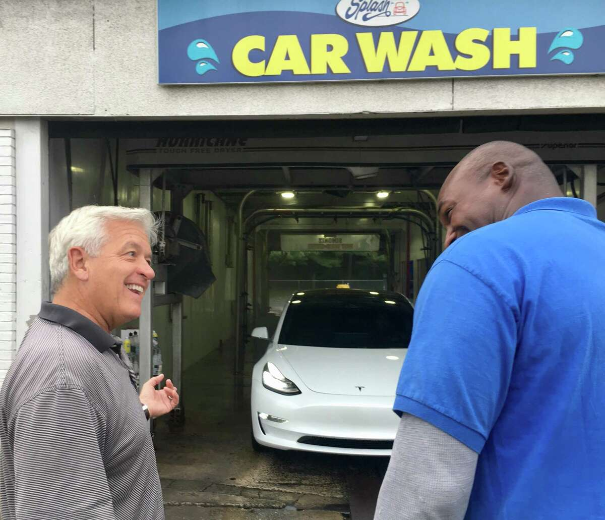 Mark Curtis, founder and CEO of Splash Car Wash, at left, is shown at the Greenwich company's Darien location, joking with an employee in 2019. Splash has been closed since the shutdown of most businesses.