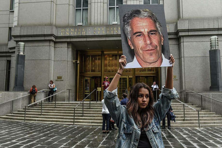 """A protest group called """"Hot Mess"""" hold up signs of Jeffrey Epstein in front of the federal courthouse on July 8 in New York City. Stephanie Keith 