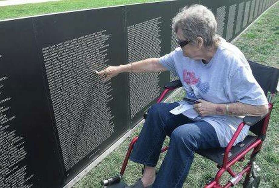 Jennifer Volk of Cooperstown spots the name of a high school classmate Thursday in Rushville on a traveling replica of the Vietnam Memorial Wall. The replica is visiting Rushville to commemorate the 100th anniversary of Smiles Day, a festival that honors Schuyler County veterans. Photo: Marco Cartolano | Journal-Courier