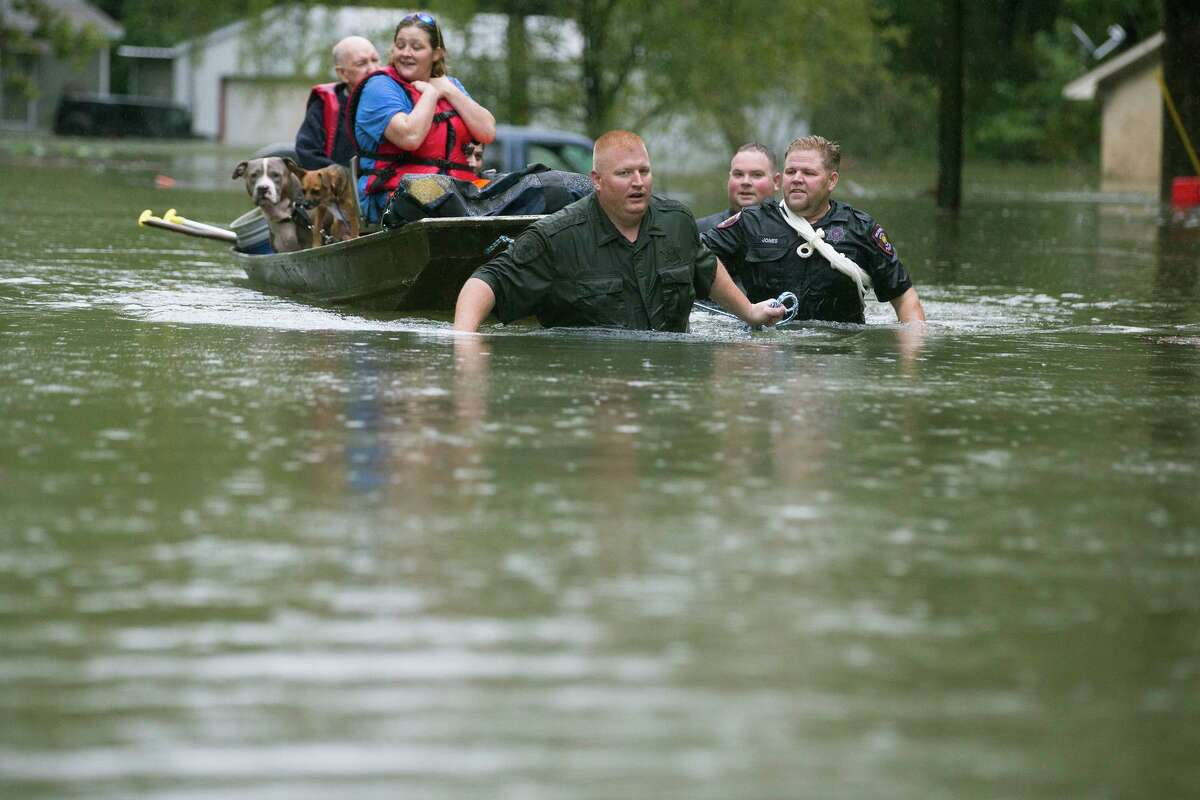 Splendora Police Lt. Troy Teller, left, Cpl. Jacob Rutherford and Mike Jones pull a boat carrying Anita McFadden and Fred Stewart from their flooded neighborhood Thursday in Splendora.