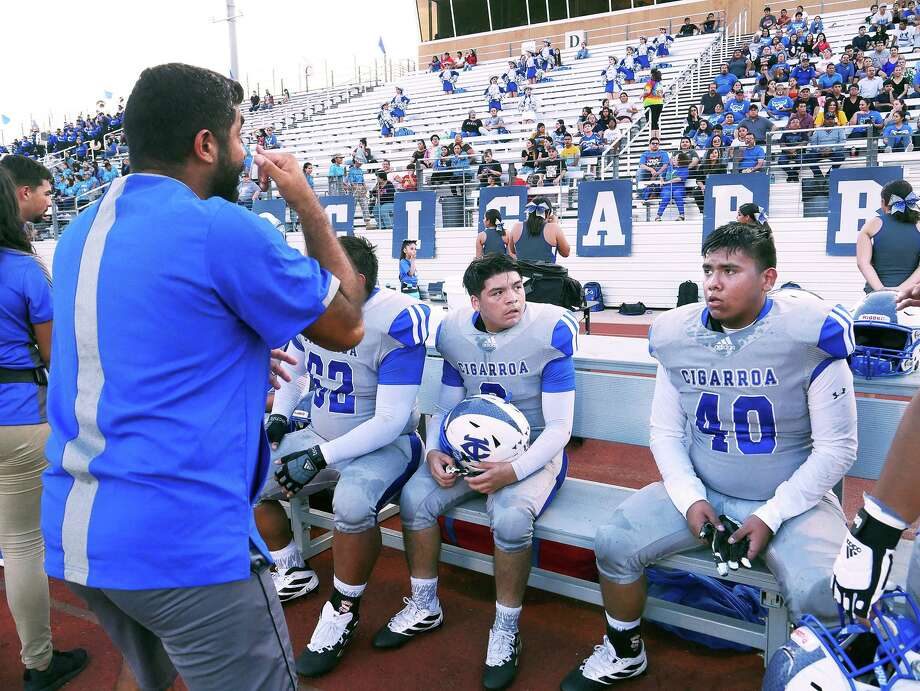 Carlos Ramos, a defensive lineman for the Cigarroa football team, looks on as his interpreter signs to him during a break in the action of a recent football game at Shirley Field. Photo: Cuate Santos / Laredo Morning Times / Laredo Morning Times