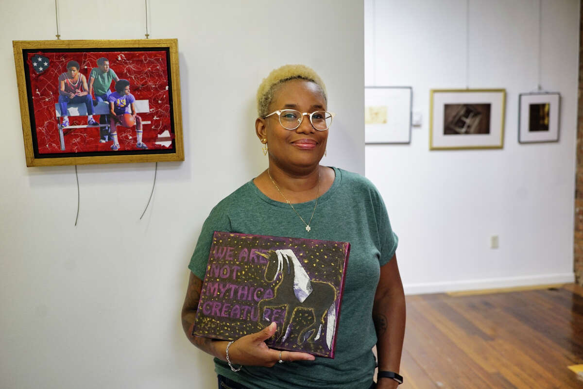 Artist and owner of PH GALLERY + STUDIO, Pilar Arthur-Snead at her gallery on Thursday, Sept. 19, 2019, in Troy, N.Y. Arthur-Snead is holding one of her mixed-media pieces, titled,