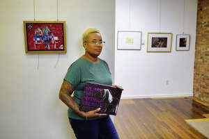 """Artist and owner of PH GALLERY + STUDIO, Pilar Arthur-Snead at her gallery on Thursday, Sept. 19, 2019, in Troy, N.Y. Arthur-Snead is holding one of her mixed-media pieces, titled, """"We Are Not Mythical Creatures: Black People"""", a piece she created as a response to being stared at on the street as a person of color.   (Paul Buckowski/Times Union)"""