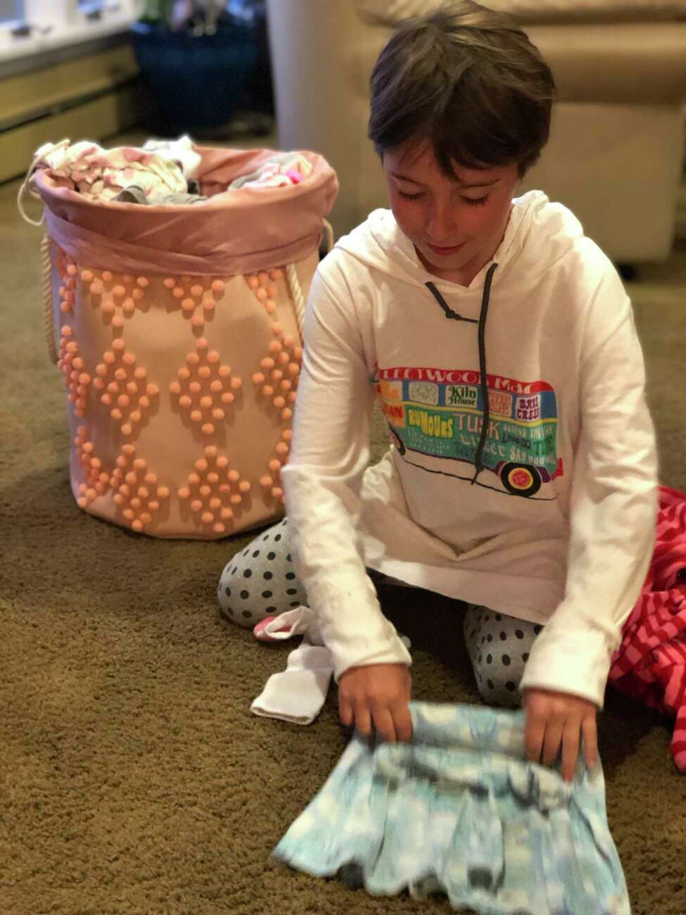 Stella Marcy, Jes Marcya€™s daughter, folds laundry.