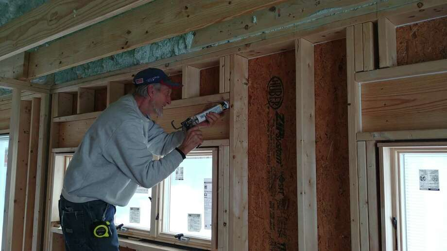 Howard Blake, a local insulation installer, caulks the wood frame of a window. Proper caulking can help to create an airtight seal. (Provided by Capital Construction)