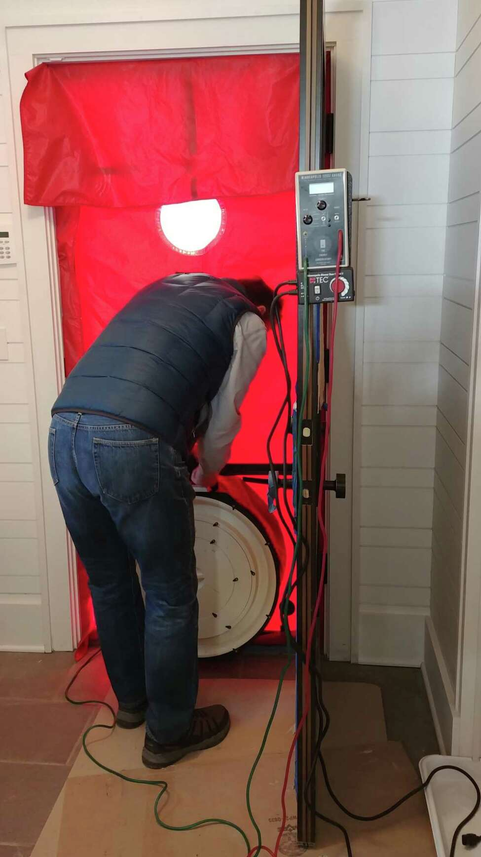Stan Grajny conducts a blower door test on a new home built by Capital Construction in Malta, N.Y. The test involves placing a powerful fan into the frame of an exterior door in order to measure the airtightness of a structure. (Provided by Capital Construction)