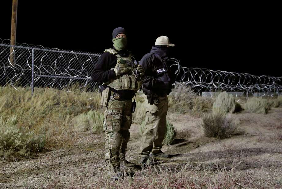 "Police officers guard an entrance to the Nevada Test and Training Range near Area 51 Friday, Sept. 20, 2019, near Rachel, Nev. People gathered at the gate inspired by the ""Storm Area 51"" internet hoax. Photo: John Locher, AP / Copyright 2019 The Associated Press. All rights reserved."