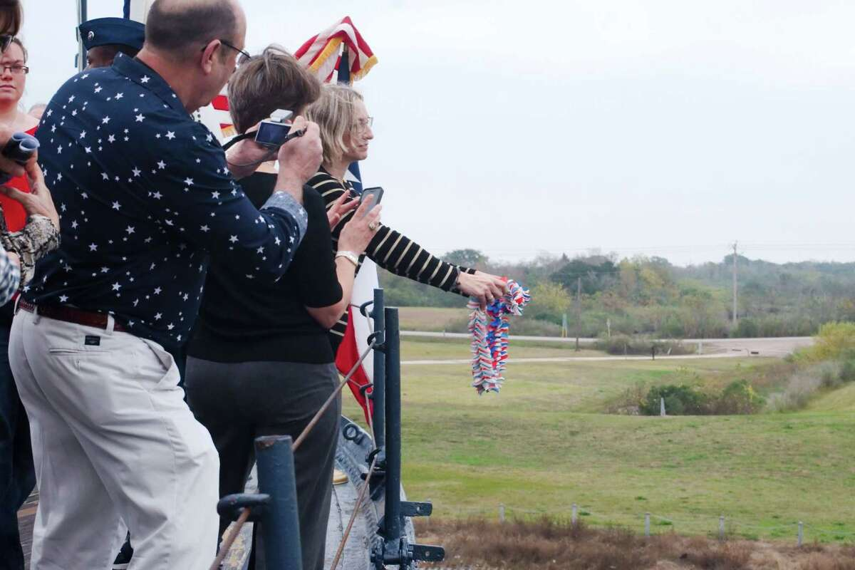 Lori LaGesse Cento, the daughter of a survivor of the Japanese attack on Pearl Harbor in 1941, tosses a wreath off the deck of the Battleship Texas in 2014 in memory of those that served and died during the attack. San Jacinto College history professor Abbie Grubb says visitors to the ship often experienced strong emotions.